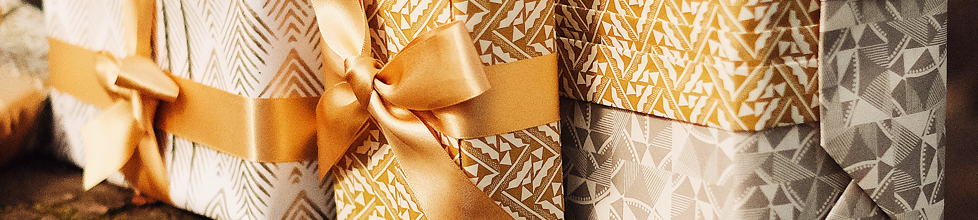 Gold and white gifts professionally wrapped in bow and eco-friendly paper